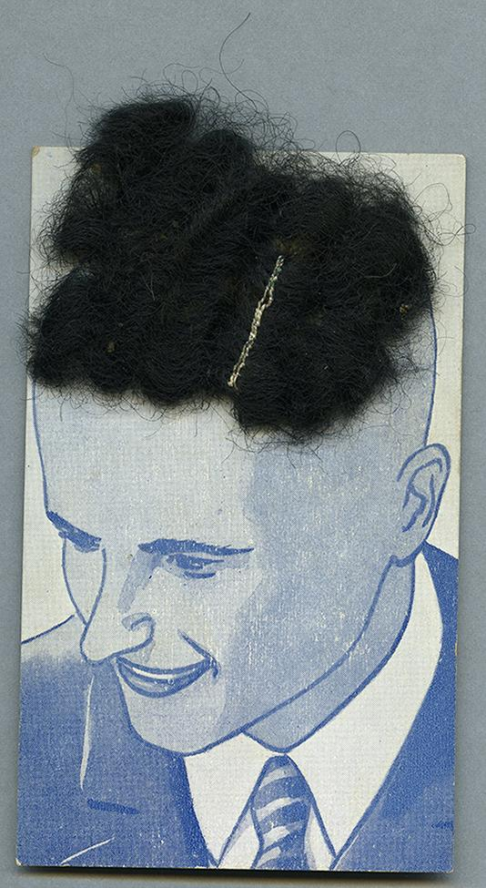 Hair clip with actual hair attached to top of packaging with ullustrated male head from the RBSC archive