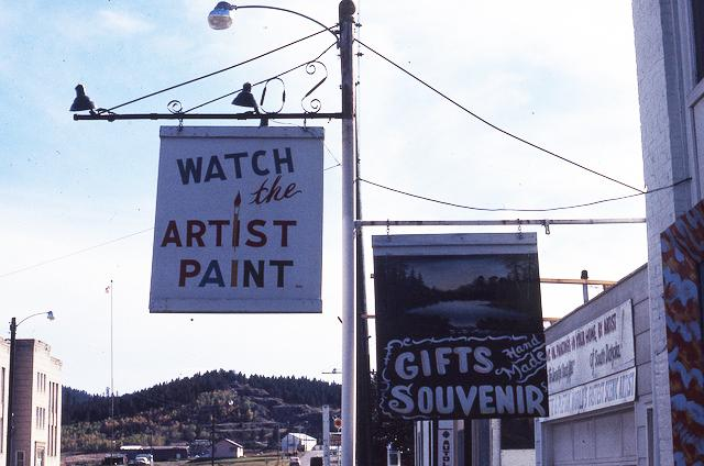"""Lamp post street sign reading """"WATCH the ARTIST PAINT"""""""