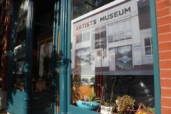 Roger Brown Study Collection storefront (north window), today, with decal of Brown's slide of Burnette G. Pletan's ARTISTS MUSEUM