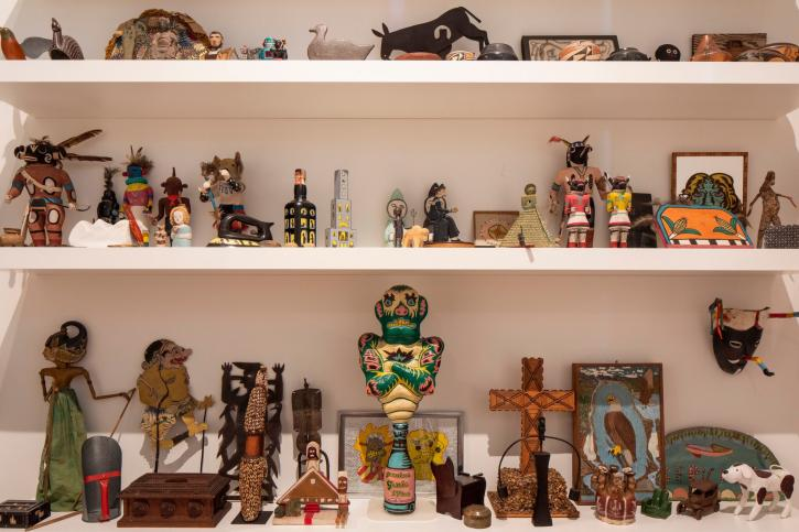 Several shelves with a collection of art objects and statues of figures, buildings, and crosses