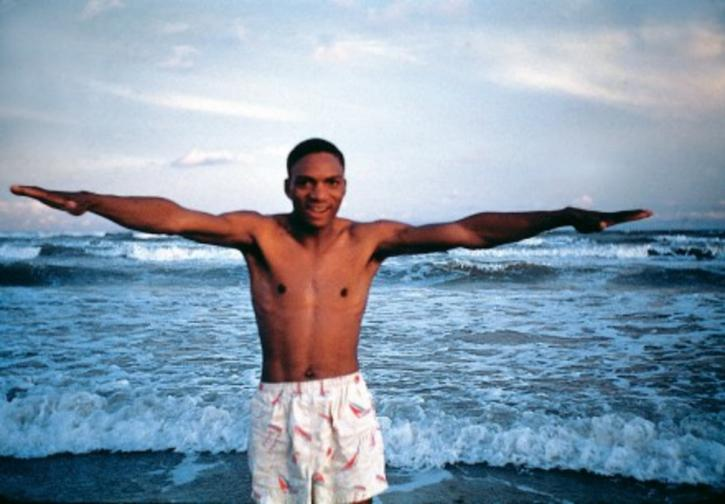 A black man in white swim trunks standing with arms outstretched on an ocean beach.