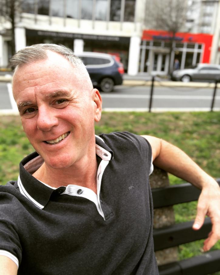 A white man is sitting on a park bench. He has short gray hair and a black short sleeved shirt with white details along the collar and buttons. He is smiling and looking into the camera.