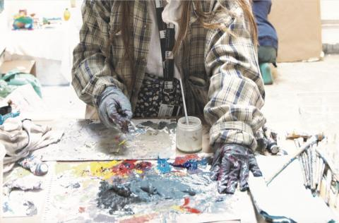 A student uses hands to work on an art project