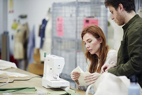 Student at sewing machine with fabric, talking to instructor.