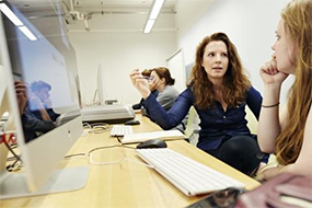 Instructor and student conversing in front of computer screen.