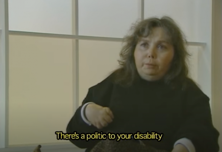 """A white woman with wispy dark hair and a black long-sleeved top is shown from the waist up. She has wispy dark hair and a black, long-sleeved top. At the bottom of the screen are yellow captions that read """"There's a politic to your disability."""""""