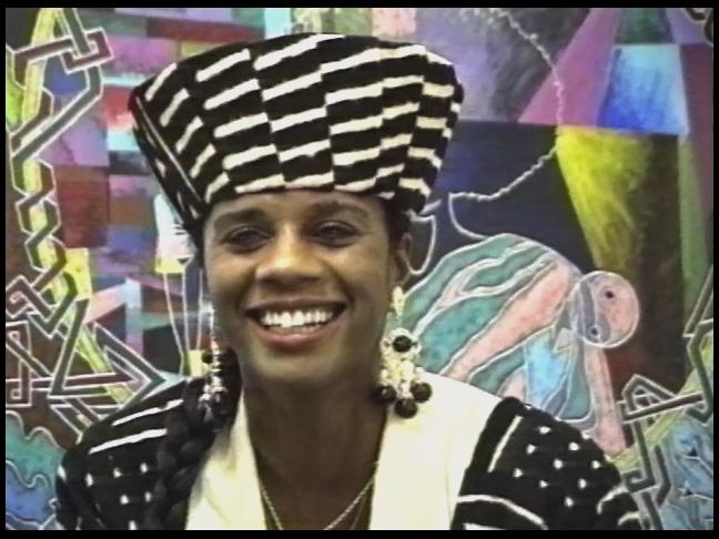 A close-up portrait of a Black woman smiling. She wears a black and white striped cone-shaped hat, chandelier earrings, a white blouse, a striped black and white coat, and two gold chains around her neck.  The background is filled with abstract shapes.