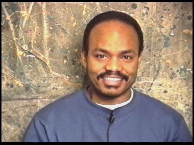 A close-up portrait of a Black man wearing a blue sweatshirt smiling and gazing directly at the camera. He has a short black afro and a mustache. A black wearable microphone is attached to his sweatshirt. The background is a muted brown canvas.