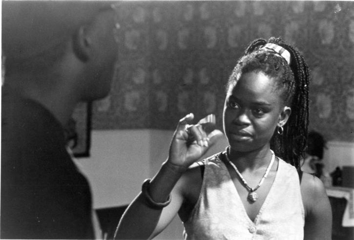 A Black woman, the actress Michelle Banks, is wearing a sleeveless button-down shirt. Her right hand is raised near her face, implying Sign Language movement.