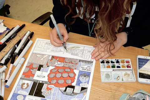 A student colors in a scene from her graphic story