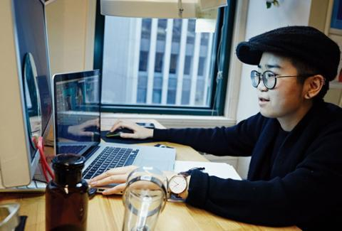 A student sits and works on laptop
