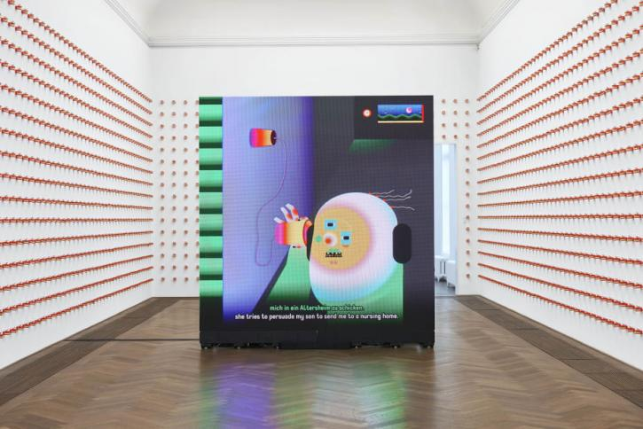 An installation of Dear Can I Give You a Hand in a white-walled gallery room. The three walls have red dentures lined neatly. In the middle of the room is a colorful square digital screen showing an animated figure holding a cup to their ear