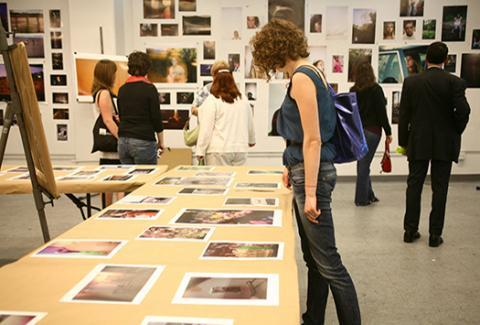 Student looking at other student's photographs on table.