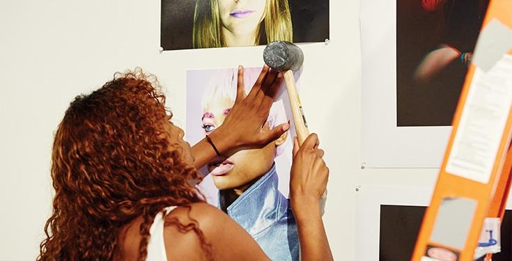 A student installs her artwork onto wall