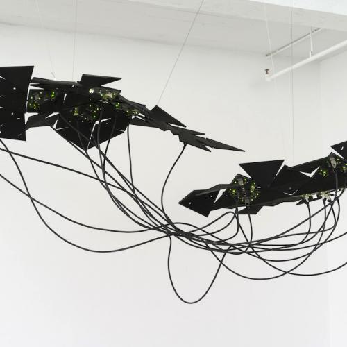 an art piece is suspended from the ceiling of a white room. It is composed of black geometric shapes connected by tangled black cords.