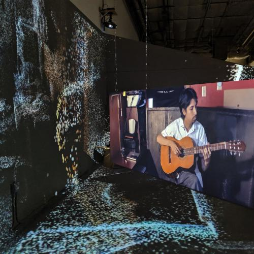 Depicts an art installation, projections and screens, with one screen depicting a musician playing a guitar.