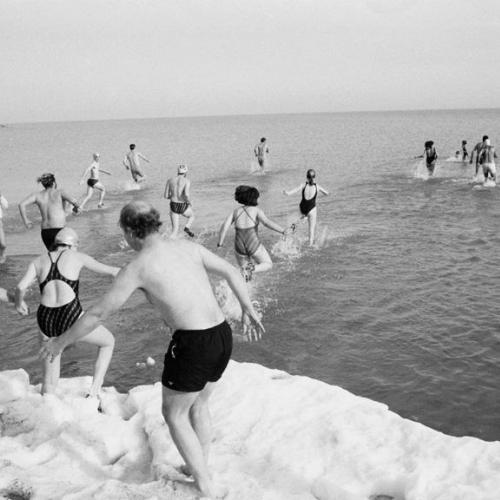 People diving into a frozen lake