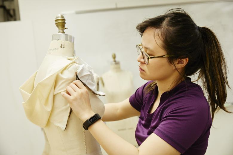 Student draping muslin over mannequin