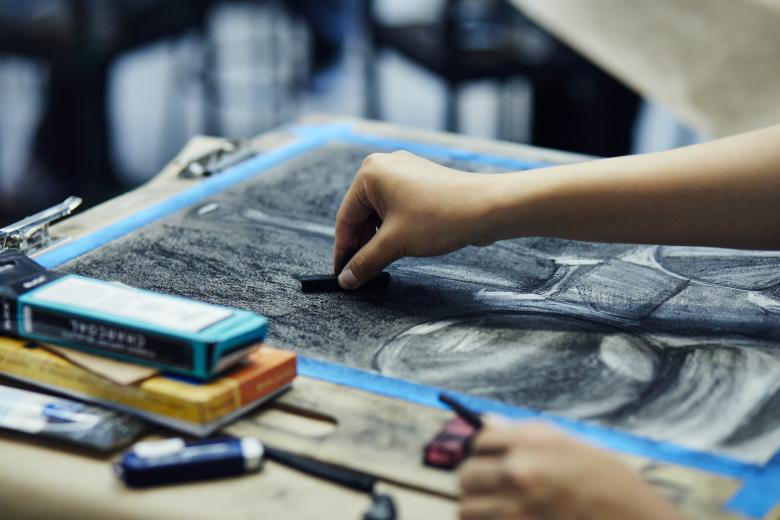 Artist working with charcoal on still life drawing