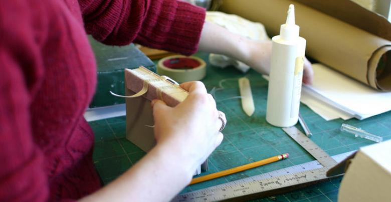 Student gluing signatures together in bookbinding class.