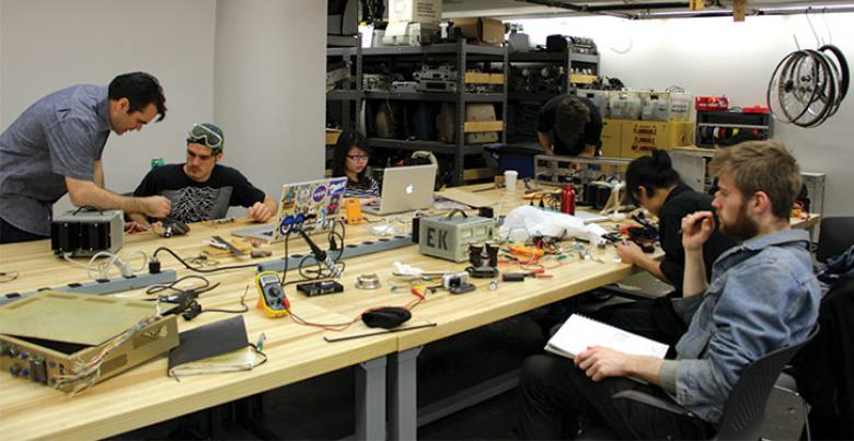 Art and Technology Students Sit around Work Table in Studio