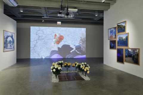 Video projection of a man holding roses on the gallery wall