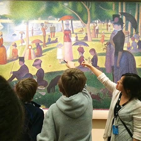 Students study the painting A Sunday Afternoon on the Island of La Grand Jatte