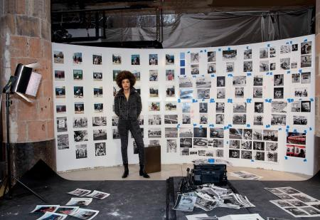 Photographer LaToya Ruby Frazier standing in front of a wall of photographs in her studio