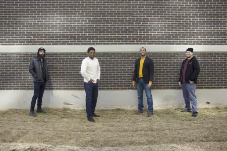 Four men stand spaced several feet apart in front of a brick wall