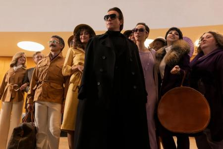 Ewan McGregor as Halston in the center, surrounded by a group of well dressed individuals.