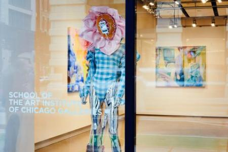 An image of a gallery window that has School of the Art Institute of Chicago Galleries stenciled on the glass. In the gallery, a figure wearing a gingham unitard with a flower headpiece is standing.