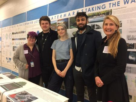 Four students and a teacher stand in front of a series of posters about conservation