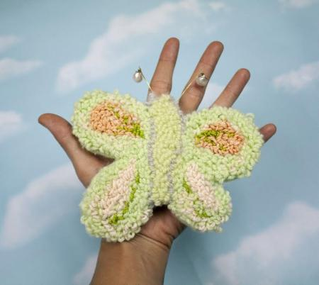 Hand holding a knit butterfly