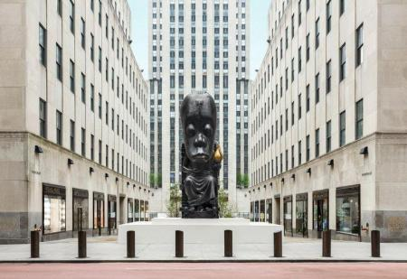 A large black statue of a seated figure with an outsized head in pictured in Rockefeller Plaza
