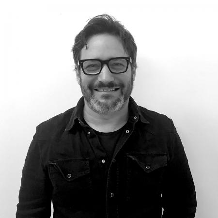 A black and white photo of a man with dark-rimmed glasses, beard, and button-up shirt against a neutral background