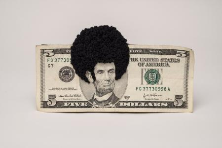 A five-dollar bill with an afro sewn on Abraham Lincoln
