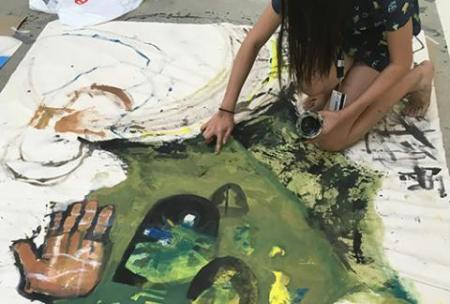 Student Painting with Green Paint