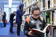 Student looking at book in Flaxman Library