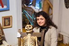 Portrait of Alessandra posing with Mexican wooden skeleton sculpture