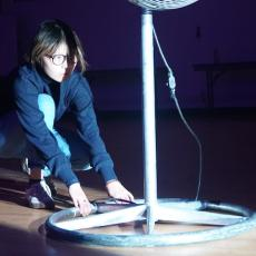 Person kneeling on ground, pushing lamp