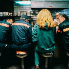 Women sitting at diner counter with back to photo