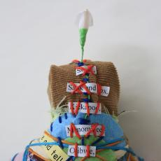 Image of doll with multi-colored stitches over unreadable text.