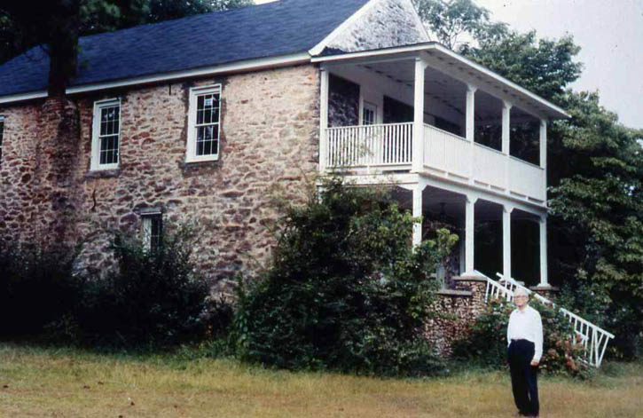 Figure 13. James Brown (Roger's father) in front of the Rock house at the completion of the renovation in 1999. Mr. Brown built the balcony, as per Roger's plans.