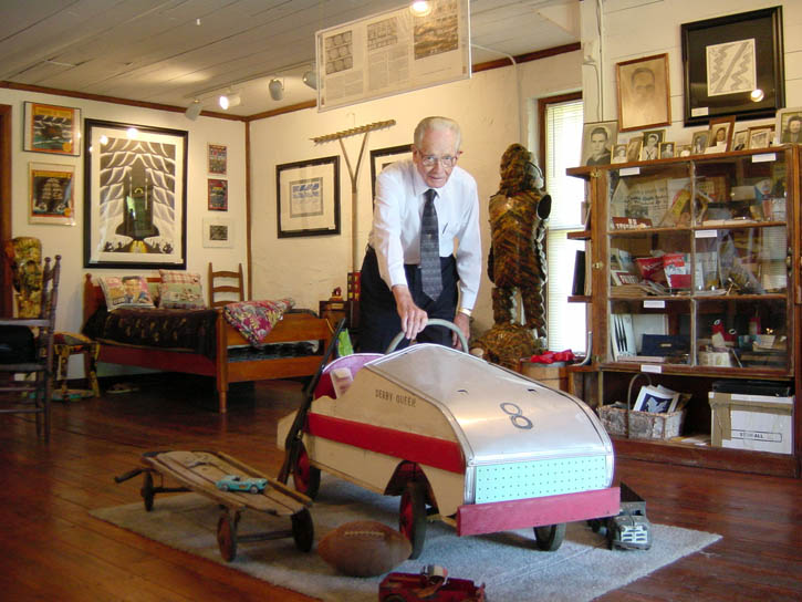 Figure 16. Mr. Brown in the Roger Brown Rock House Museum, with the soap box derby car he built for Greg Brown many years before.
